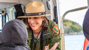 Park ranger talks with a visitor on a boat program.