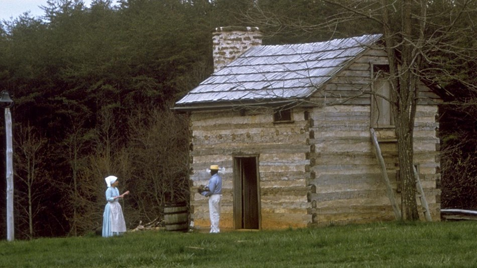a rustic cabin with two individuals standing out front