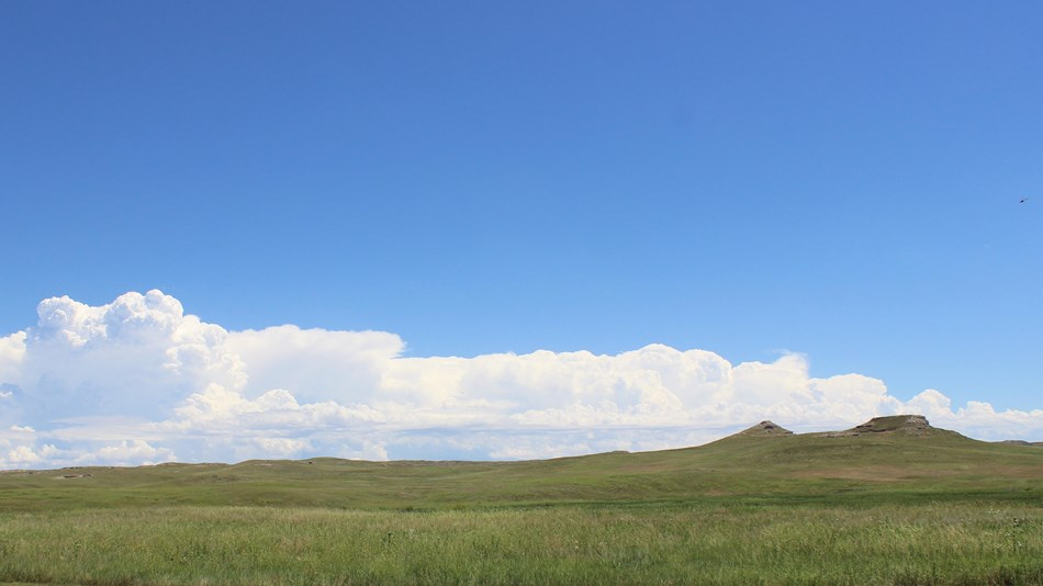 The Agate Fossil Beds with fluffy clouds.