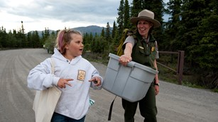 a park ranger in Denali speaks with a young girl while carrying supplies