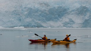 two kayakers paddle through icy waters near a glacier