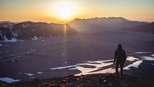 a hiker stands on a ridge watching sunset over a river valley