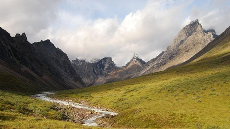 the Arrigetch Peaks in Gates of the Arctic National Park with a river in the foreground