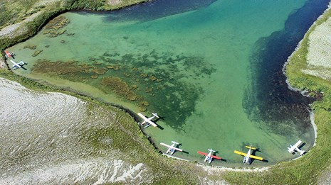 float planes docked along the shore of an inlet in turquoise waters