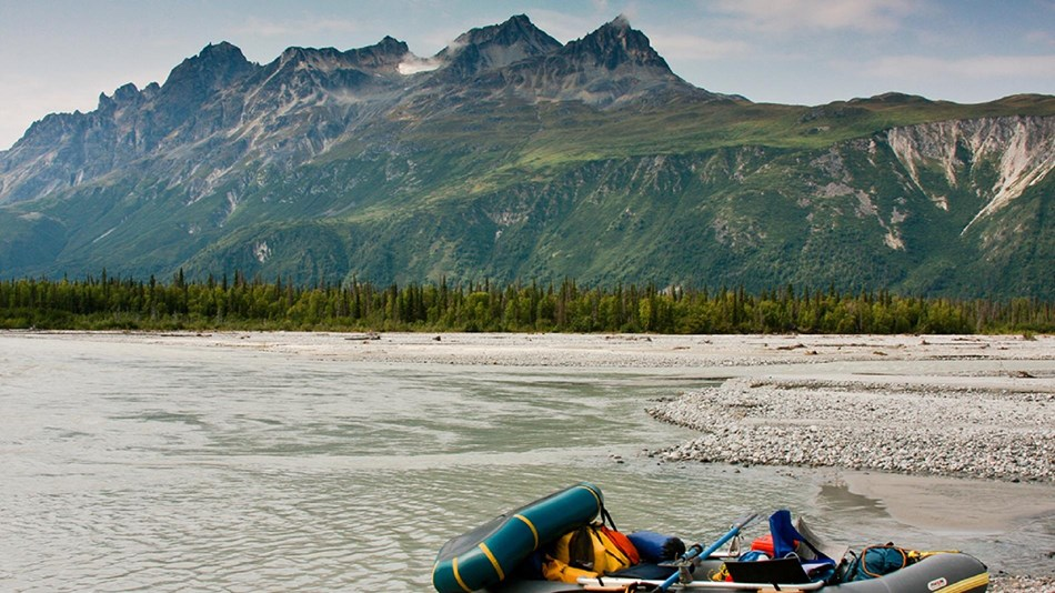 a raft packed with gear sits at the edge of a slow-moving river, with mountains in the background