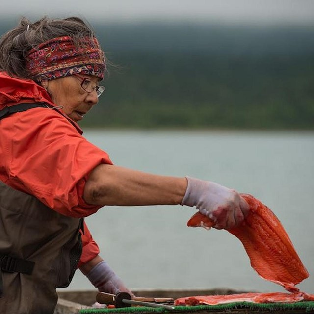 a young girl holds a piece of salmon by a river