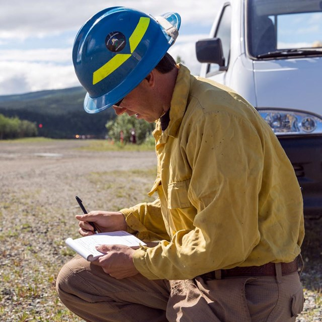 A wildland fire crew member kneels down in gravel to fill out his time sheet.
