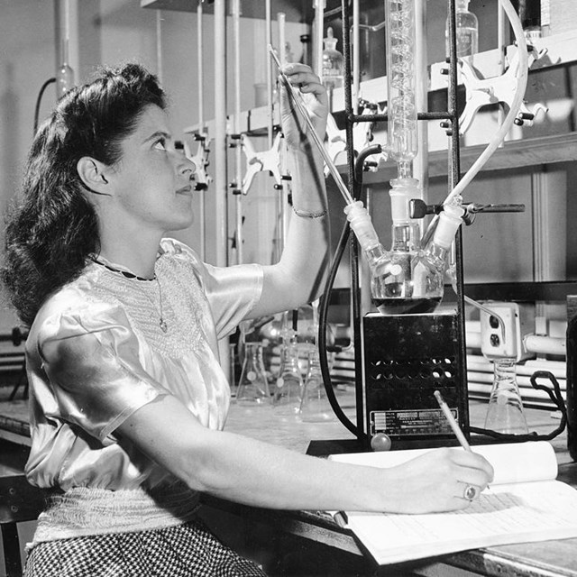 a woman looks at a glass object at a laboratory desk