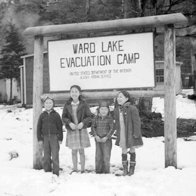 Black and white photo of four children in front of Ward Lake Evacuation Camp sign.