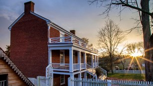 East side of McLean House with both front porches and ice house at sunset