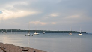 A number of sailboats are anchored out in the lake, just off of a sandy beach.