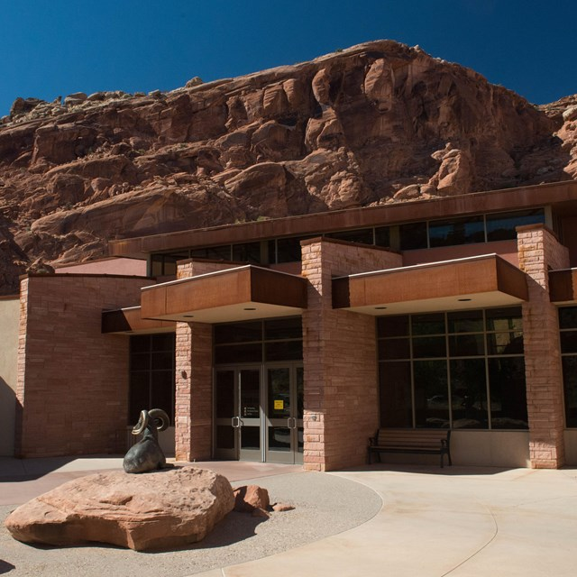 a tan building with high red-rock cliffs in the background