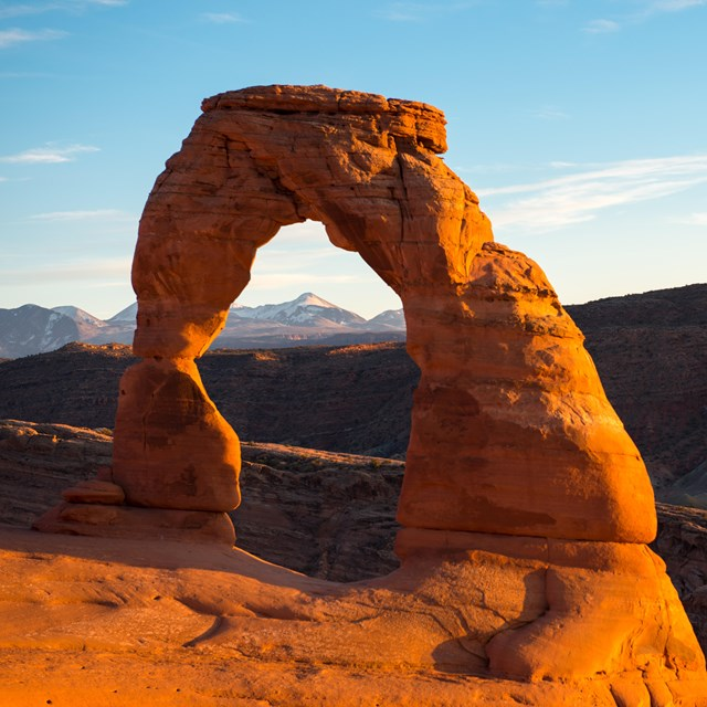 a red rock arch with snow-capped mountains in the background