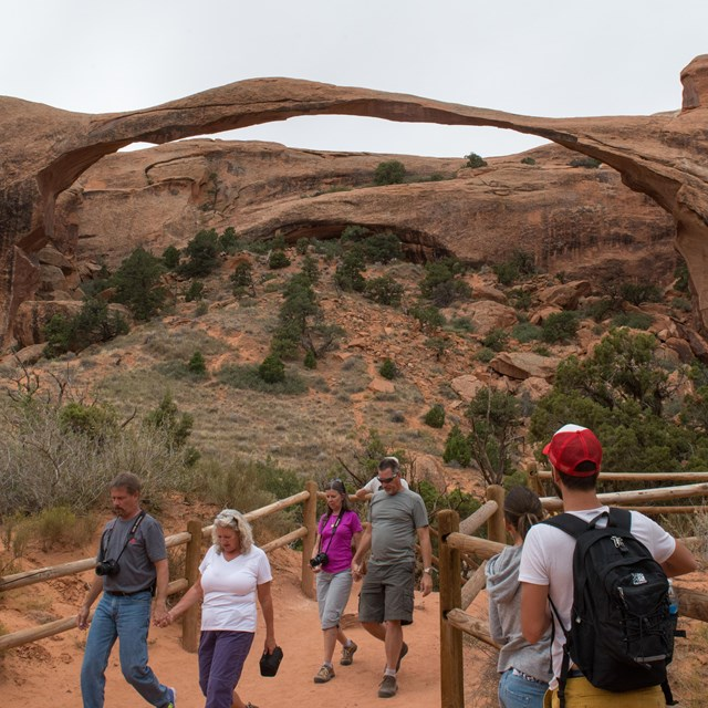 a group of people view a broad, thin arch