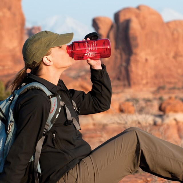 a woman drinks water from a red bottle