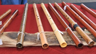 Row of wooden flutes lined up on red tablecloth