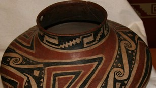 Clay pot decorated with red and black designs