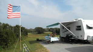 Camping site with RV, picnic table, chairs and American flag