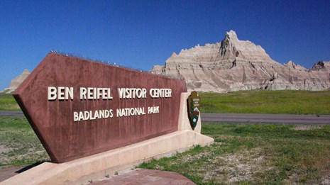 Picture of the Ben Reifel Visitor Center Sign with Badlands Formation in the Background.