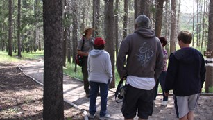 Male park ranger and four visitors on a forested trail.