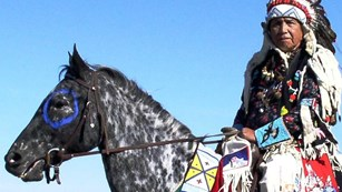 Nez Perce man in full regalia riding an apaloosa horse.