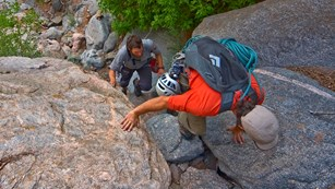 three hikers scrambling up steep rock ledges, viewed from above