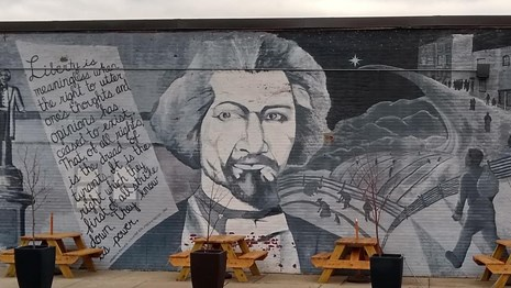 Mural of Frederick Douglass with his portrait in the center and a quote to the left.