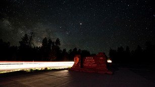 Entrance sign for Bryce Canyon National Park beneath the Milky Way