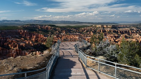 View of empty fenced viewpoint overlooking red rocks and green forest