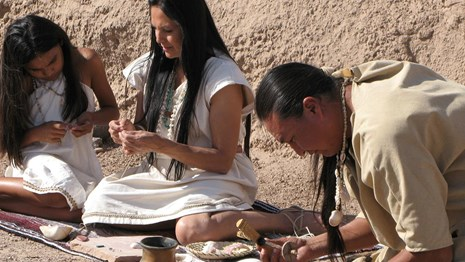 scene from park film with 3 costumed actors making jewelry with stone tools