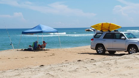 Visitors enjoying the beach after using their vehicle to get out onto the beach.