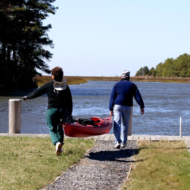 Two people carry a kayak towards a boat launch.
