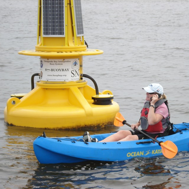 A kayaker in front of a NOAA interpretive buoy on the trail
