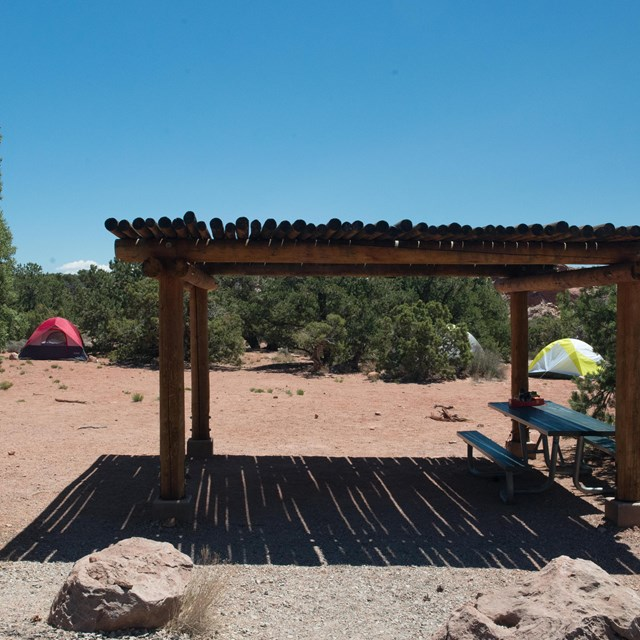 a shade structure, picnic table, and two tents