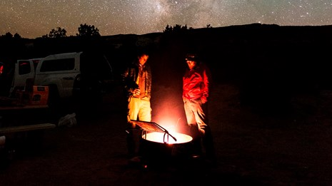Two people stand beside a campfire, with the Milky Way above them.