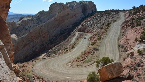 Gravel switchbacks and car in dramatically uplifted landscape.