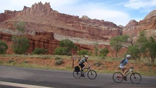 Two bike riders on paved highway, with scenic rock formations and blue sky in the background.
