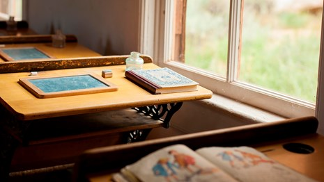 Photo of old-fashioned school books on old-fashioned desks beside windows.