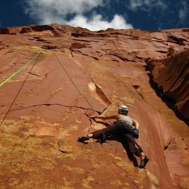 Person climbing red cliff wall with blue sky and clouds above.