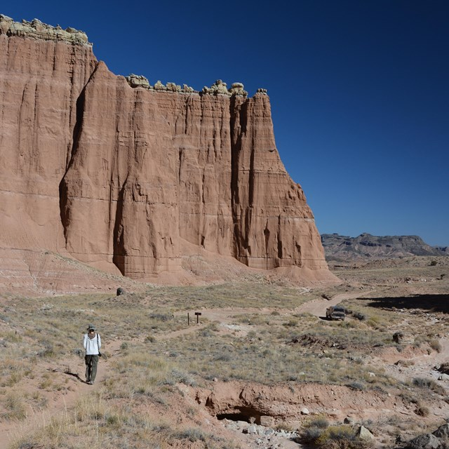 Person hiking on dirt trail below big red cliffs and blue sky, with a car parked in the distance.