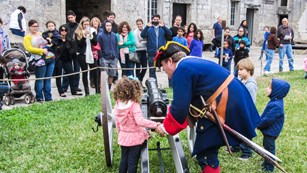 A group of people watch a young visitor being instructed by a ranger dressed as a 1740s soldier.
