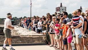 large group of visitors attending a cannon demonstration on Castillo's gundeck
