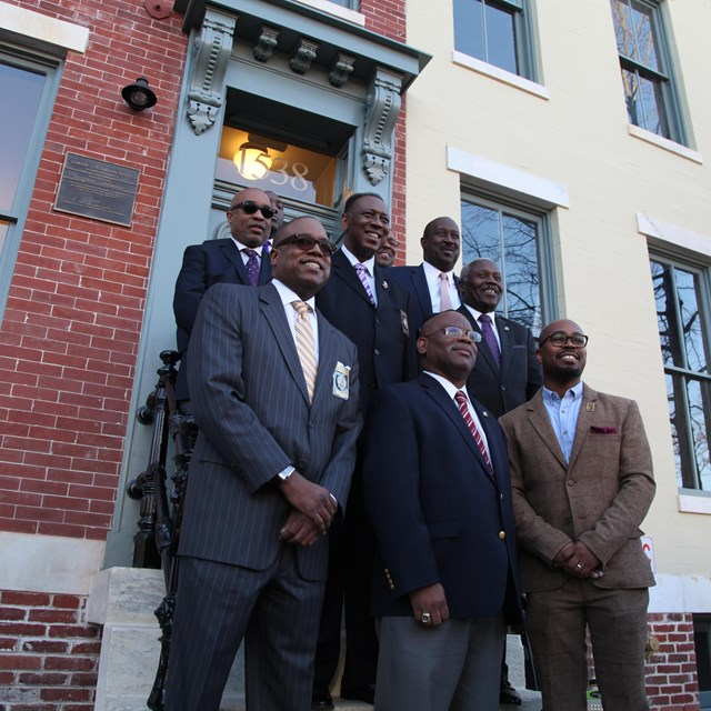 Members of Omega Psi Phi Fraternity, Inc. stand outside the Woodson Home