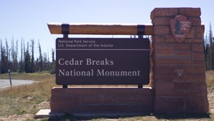 Stone and wood sign for Cedar Breaks National Monument.