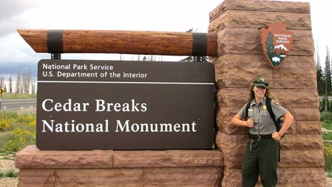Park ranger standing in front of stone and wood sign for Cedar Breaks National Monument.