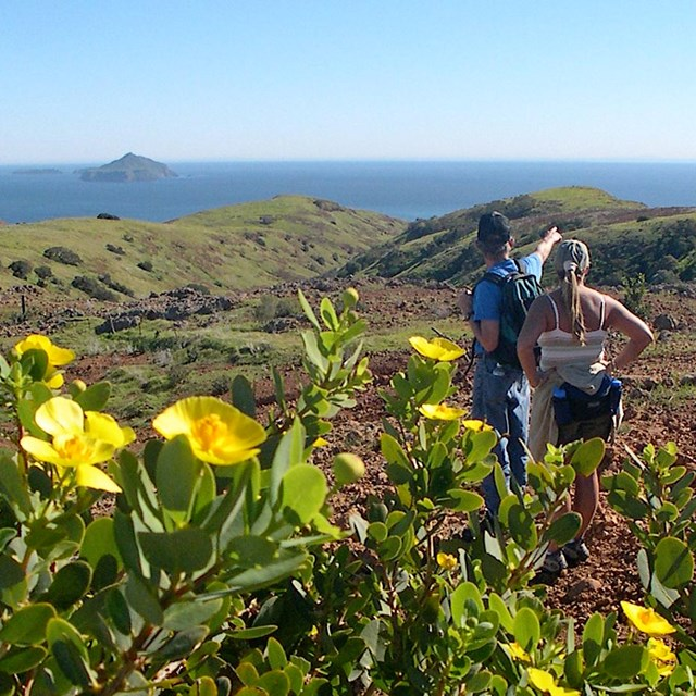 Hikers on mountain overlooking ocean and islands. ©Kathy de-Wet Oleson