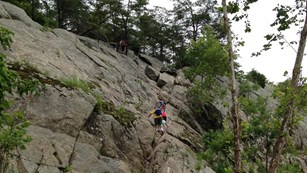 Visitors hiking up the 40 foot traverse on Billy Goat Section A trail.