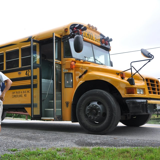 Ranger stands near school bus delivering students for field trip.