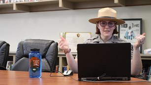 A ranger presents a virtual program on a laptop in the site's library.