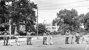 Soldiers stand behind barricades in front of Central High School during the 1957 integration crisis.